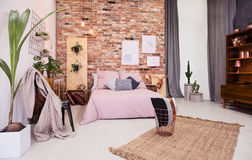 Dusty pink bedroom. With bed and red brick wall royalty free stock photo