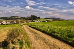 Dusty road. Dirt road in the middle of pastures ending in the village Stock Images
