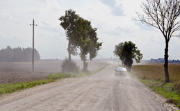 Dusty rural gravel road between farm fields Stock Photography