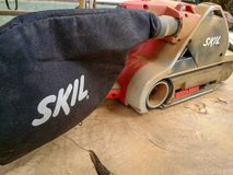 Dusty Skil brand electric sander on smoothen tropical timber in stock photography