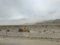 Dusty Storm en desierto con las montañas en fondo Fotografía de archivo libre de regalías