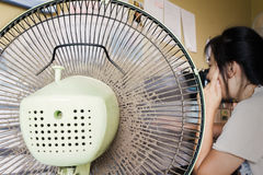 Dusty or unclean portable fan with blurred girl working at table Stock Image