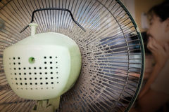 Dusty or unclean portable fan with blurred girl working at table Royalty Free Stock Image