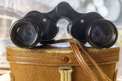 Dusty vintage binoculars sitting on top of leather case on soft Royalty Free Stock Image