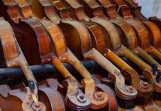 Dusty violins in rack Royalty Free Stock Image