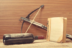 Dusty wine bottle, crossbow and photo album Royalty Free Stock Photo