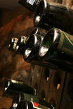Dusty wine bottles. On a rack in a cellar Royalty Free Stock Photo