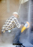Dusty work. A worker drilling through some wall tiles using a mechanical rotary drill Stock Photography