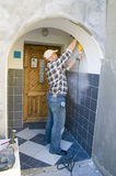 Dusty work. A worker drilling through some wall tiles using a mechanical rotary drill Stock Image