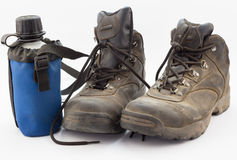 Dusty worn hiking boots with blue water bottle Royalty Free Stock Photos