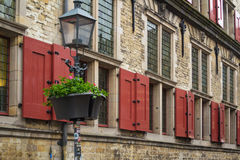 Dutch. Archtecture found in Delft, the netherlands, right side of the central cathedral, red wooden  windowpanes and flowerbed hung on street lamp Stock Photos