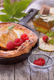 Dutch baby pancake with apple cinnamon and fresh. Dutch baby pancake with apple and cinnamon and fresh raspberries on wooden table Stock Images