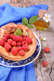 Dutch baby pancake with apple cinnamon and fresh. Dutch baby pancake with apple and cinnamon and fresh raspberries on wooden table Royalty Free Stock Images