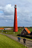 Dutch bicyclists. Characteristic view of Dutch provincial landscape with bicycle riders and lighthouse, in the Noord Holland seaside town of Den Helder, the Stock Image
