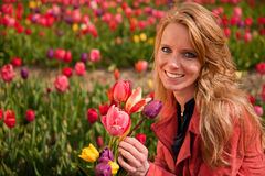 Dutch blond girl in field with tulips Royalty Free Stock Photo