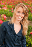 Dutch blond girl in field with tulips Royalty Free Stock Images