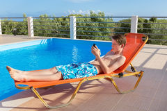 Dutch boy on sunlounger operating mobile phone at pool. Caucasian youngster lying on sunlounger operating mobile phone at swimming pool royalty free stock images