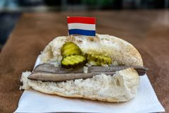 Dutch broodje haring. Traditional dutch snack, seafood sandwich with herring, onions and pickled cucumber. Broodje haring on the wooden table. With flag of stock photos