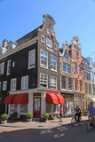 Dutch buildings and tourists in Old Town of Amsterdam, Netherlan Royalty Free Stock Photo