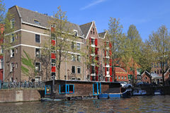 Dutch buldings and houseboat along canal, Amsterdam Stock Photography
