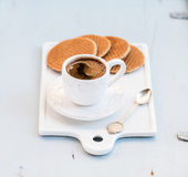 Dutch caramel stroopwafels and cup of black coffee on white ceramic serving board over light blue wooden backdrop Stock Photos