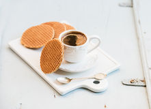 Dutch caramel stroopwafels and cup of black coffee on white ceramic serving board over light blue wooden backdrop Royalty Free Stock Photos