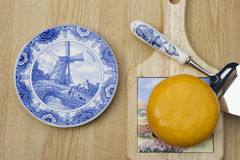 Dutch Cheese. A Delft plate, a cutting board, Dutch cheese and a cheese cutter. This is cheese the Dutch way. Cheese is great for the teeth royalty free stock photos