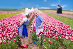 Dutch children in tulip field. Happy Dutch children playing in blooming tulip flowers field.  Boy and girl wearing traditional national costume, wooden clogs and Stock Photo