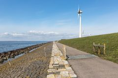 Dutch coastline with dike and wind turbines Royalty Free Stock Images