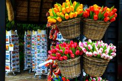 Dutch colorful wooden tulips, postcards in souvenir shop, Netherlands, Europe. Breathtaking colorful bouquets of wooden tulips in the basket, wooden shoes on Royalty Free Stock Image