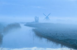 Dutch dawn. Foggy dawn at the water and a windmill in the Dutch countryside Royalty Free Stock Images