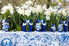Dutch delfter porcelain dolls and tiles in new flower tub. Typical dutch blue and white Delft porcelain flower tub and White daffodils Stock Image