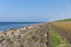 Dutch dike along the sea with wind turbines Royalty Free Stock Images