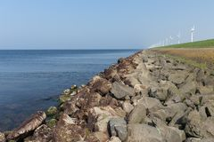 Dutch dike along the sea with wind turbines Royalty Free Stock Photo