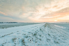 Dutch dike covered with snow in winter Stock Photos
