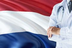 Dutch Doctor standing with stethoscope on Netherlands flag background. National healthcare system concept, medical theme royalty free stock images