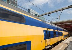 Dutch double decker train is leaving a station. Dutch yellow double decker train is leaving a station Royalty Free Stock Photo