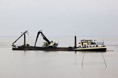 Dutch dredger in Dollard near Nieuw Statenzijl. The Dollard area, which borders the Eems estuary, came into existence between 1280 and 1550 approximately.  Under Stock Photography