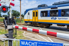 Dutch electric train going through crossing Royalty Free Stock Images
