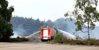 Dutch extinguishing fire brigade. The dutch fire brigade is extinguishing a heath fire with big jets of water Stock Images