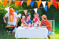 Dutch family having grill party in garden. Happy big Dutch family with kids celebrating a national holiday or sport victory having fun at a grill party in a Royalty Free Stock Photography