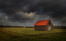 Dutch farm house. A dutch farm house with dark clouds Royalty Free Stock Images