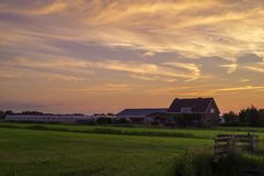 A dutch farmhouse on the country side at sunset / dusk stock photo