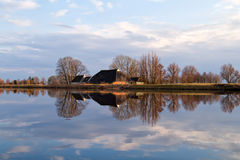 Dutch farmhouse by river before sunset Stock Images