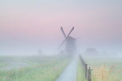 Dutch farmland with windmill in fog Royalty Free Stock Photos
