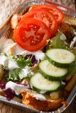 Dutch fast food kapsalon of french fries, chicken, fresh salad a. Nd sauce close-up in a foil tray on the table. vertical stock photography