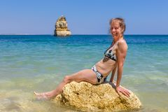 Woman wearing bikini sits on rock in sea royalty free stock image