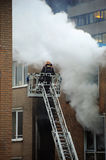 Dutch fireman on the job. A fireman atop a ladder platform surrounded with smoke tending to a small domestic fire in an apartment building Royalty Free Stock Photos