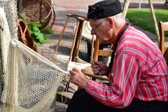 Fisherman working at his fishnet. Dutch fisherman sitting on the chair and working at his fishnet close up view Royalty Free Stock Photos
