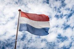 Dutch flag against a cloudy sky Royalty Free Stock Photography